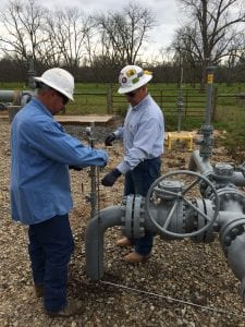 two workers checking pipeline equipment